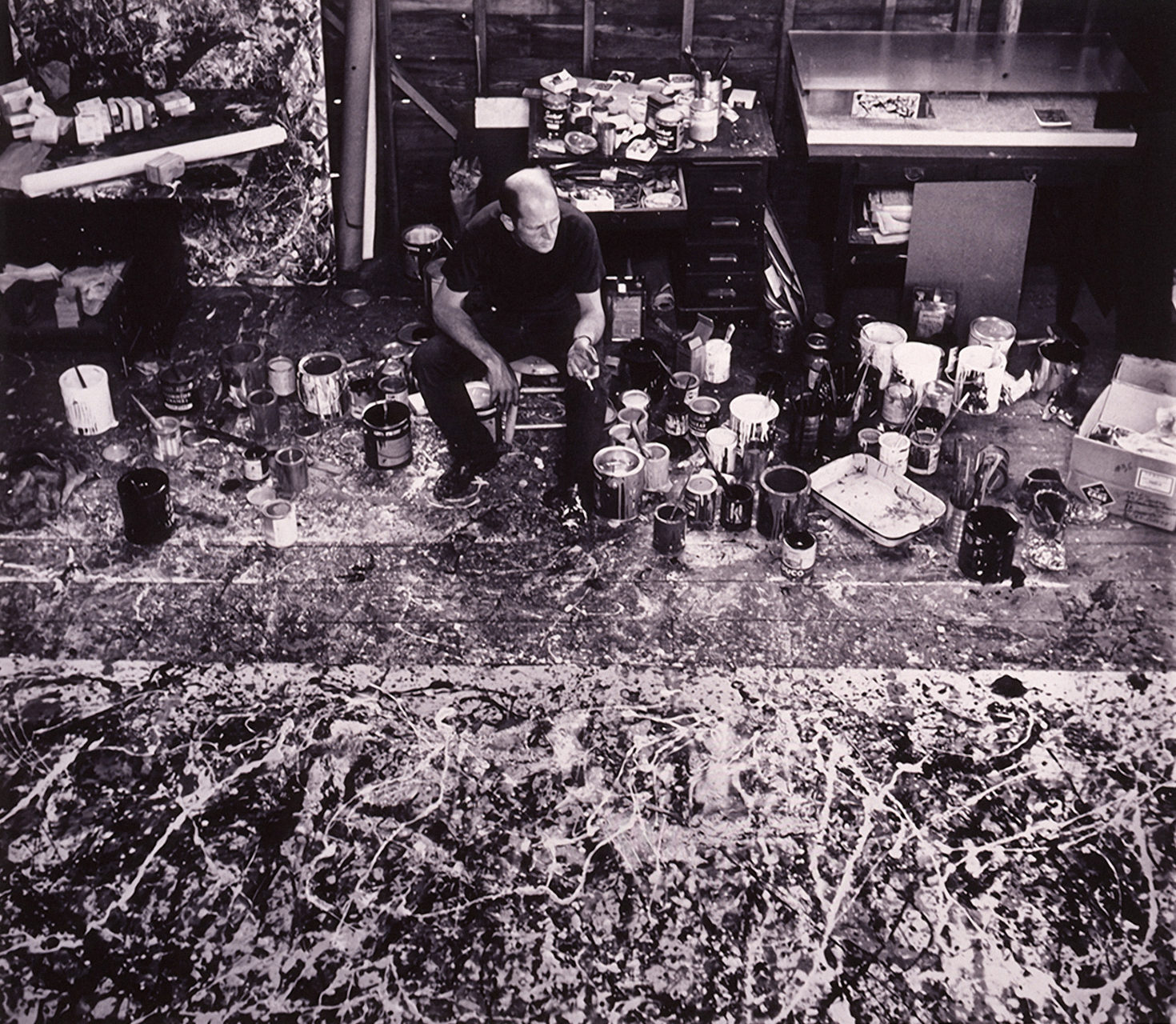 Jackson Pollock is seated in his studio in 1950, surrounded by paint tins. There is a large painting on the floor. Photograph by Hans Namuth